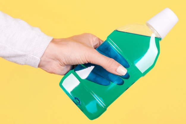 Hand mit mundwasserflasche, zahnpflege isoliert
