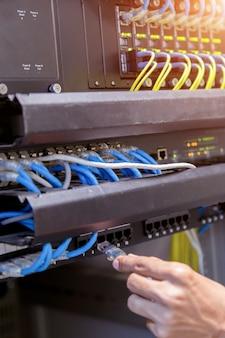 Hand mit netzwerkkabeln, die an server in einem datencenter angeschlossen sind