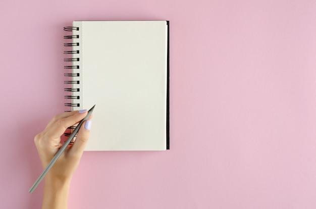 Hand mit notizblockzusammensetzung auf rosa hintergrund.