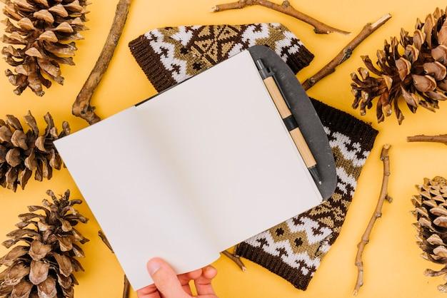 Hand mit notizbuch zwischen zweigen und hindernissen