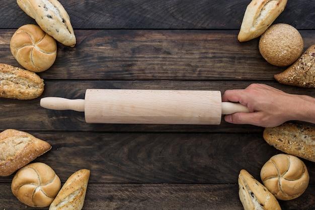 Hand mit nudelholz auf dem desktop mit bäckerei