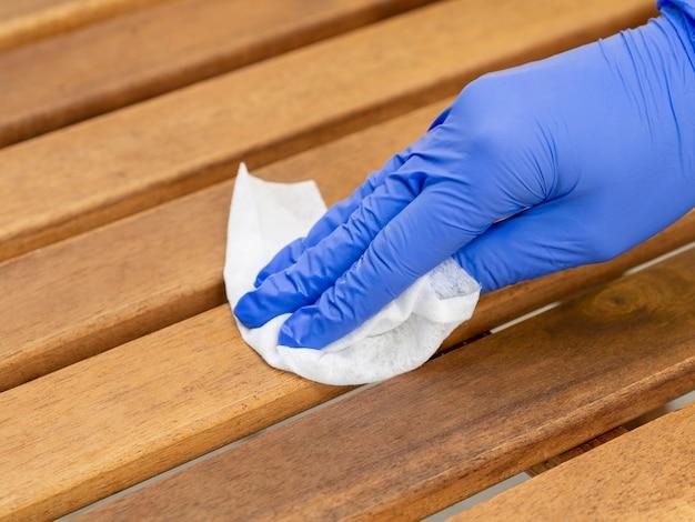 Hand mit op-handschuh zur desinfektion der holzoberfläche
