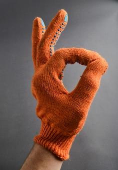 Hand mit orangefarbenen arbeitshandschuhen zeigt daumen symbol in ordnung.