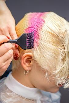 Hand mit pinsel, der weißes haar der frau in der rosa farbe am friseursalon färbt