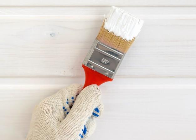Hand mit pinsel in weißer farbe