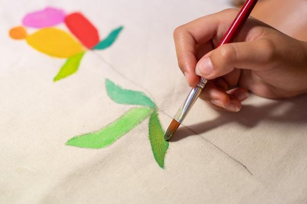 Hand mit pinsel malen handwerk auf einem stoff