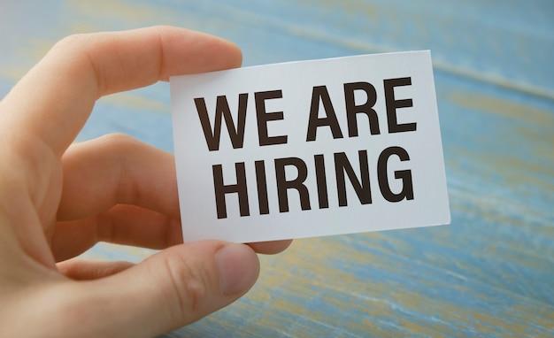 Hand mit plakat plakat mit text: jetzt einstellen, auf grauem hintergrund isoliert. job finden, jobkonzept suchen.