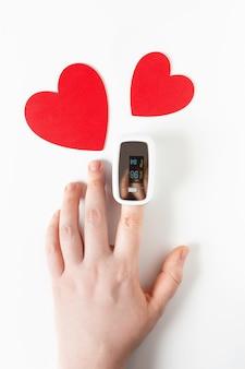 Hand mit pulsoximeter am finger und herzsymbol
