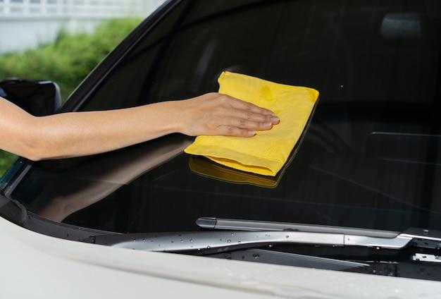 Hand mit reinigungstuch des mikrofasertuchs des autos
