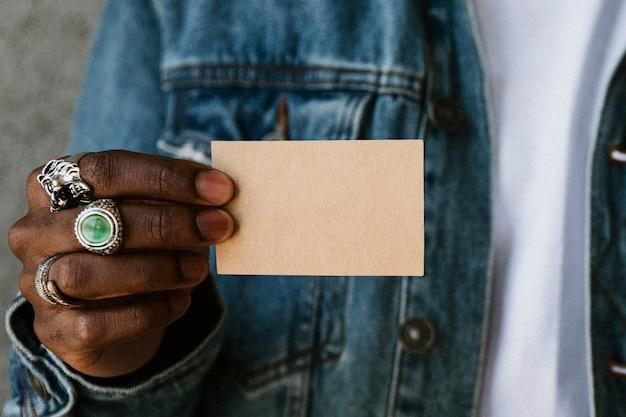 Hand mit ringen, die ein namenskartenmodell halten
