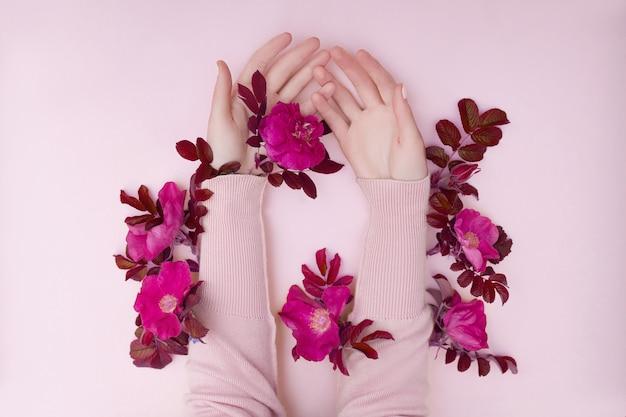 Hand mit rosa blumen und blumenblättern, die auf einer papieroberfläche liegen. kosmetik für die handpflege. natürliche blütenkosmetik, ätherische öle, anti-falten- und anti-aging-handpflege