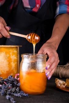 Hand mit schöpflöffel, der honig aus einem glas honig auswählt.