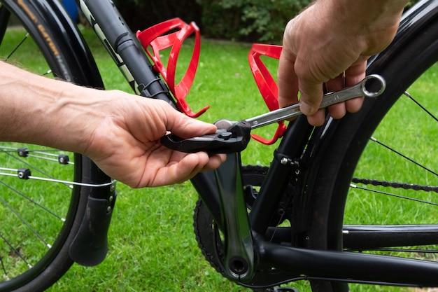 Hand mit schraubenschlüssel, der fahrradpedale auf dem gras befestigt