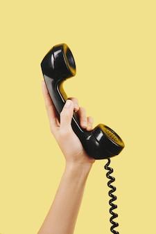 Hand mit schwarzem telefonhörer