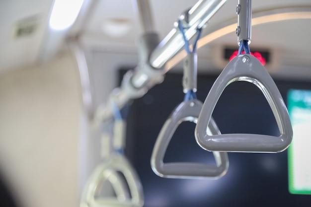 Hand mit sicherheitsgurten, hängenden griff, kunststoff-haltegriff im öffentlichen verkehr