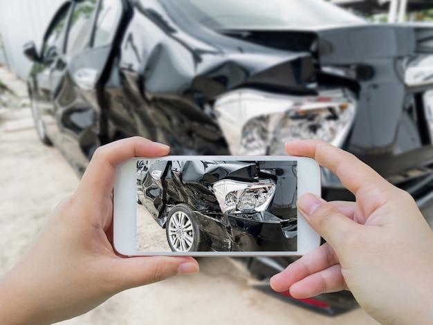 Hand mit smartphone, das foto des autounfalls macht