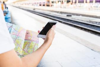 Hand mit Smartphone und Karte