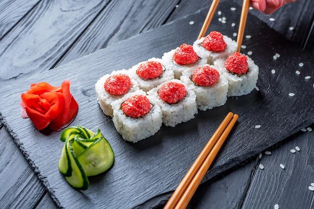 Hand mit stäbchen nimmt sushi von seth-sushi-rollen mit frischkäse, reis und lachs auf eine schwarze tafel, die mit ingwer und wassabi auf einem dunklen holztisch dekoriert ist. japanisches essen