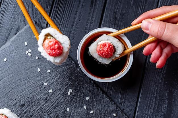 Hand mit stäbchen nimmt sushi von sushi-rollen mit frischkäse, reis und lachs auf schwarzem brett, dekoriert mit ingwer und wassabi auf dunklem holztisch. japanisches essen. selektiver weichzeichner