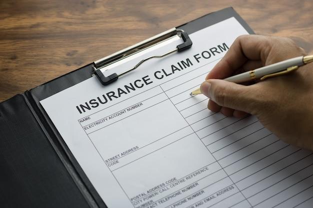 Hand mit stift auf antragsformular für die anmeldung anspruch krankenversicherung