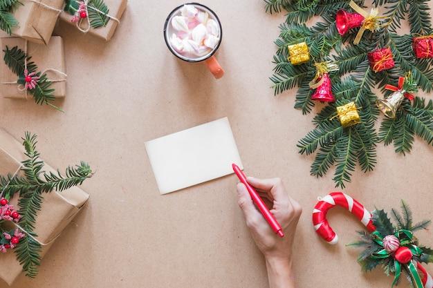 Hand mit stift nahe papier nahe präsentkartons, weihnachtszweig und -cup