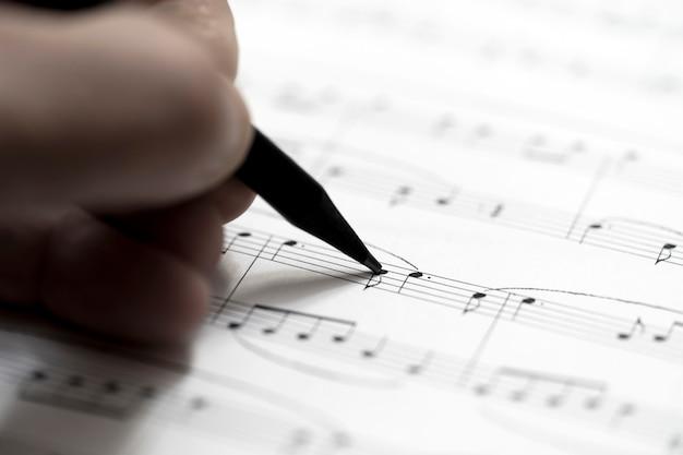 Hand mit stift und notenblatt - musikalischer hintergrund