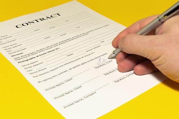 Hand mit stift unterschreibt einen vertrag