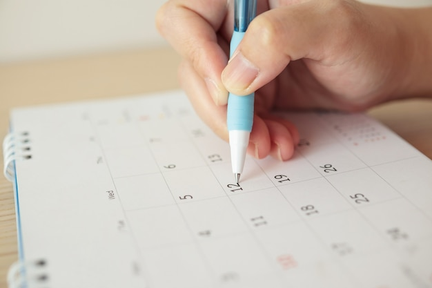 Hand mit stiftschreiben am kalenderdatum
