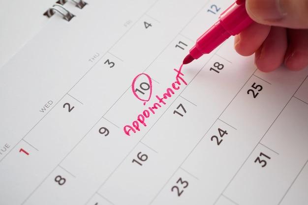 Hand mit stiftschreiben auf kalenderdatumsterminkonzept