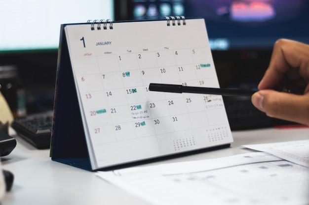 Hand mit stiftspitze auf kalenderseite