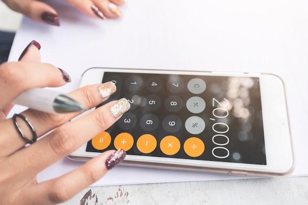 Hand mit taschenrechner auf handy. hand von geschäftsarbeitsdokumenten über verlust und profit