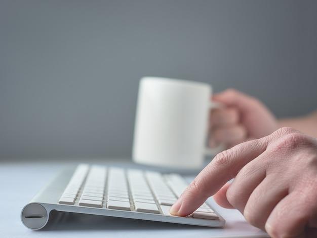Hand mit tastatur und einer tasse tee