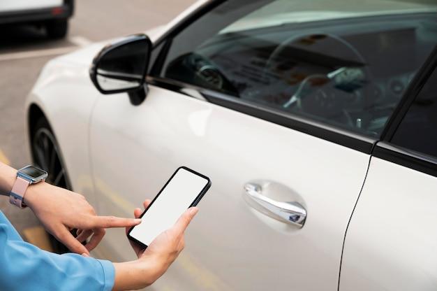 Hand mit telefon, um auto zu verriegeln
