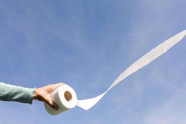 Hand mit toilettenpapierrolle