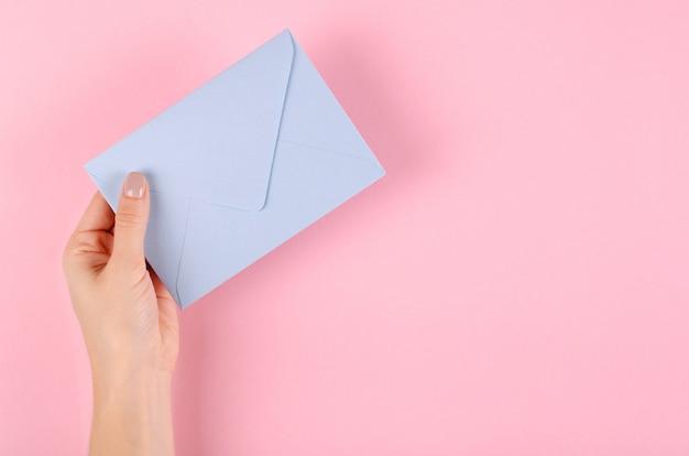 Hand mit umschlagzusammensetzung des blauen papiers auf rosa hintergrund.