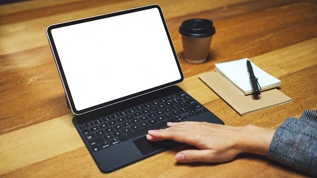 Hand mit und berühren tablet-tastatur mit leeren weißen desktop-bildschirm als computer-pc, kaffeetasse auf holztisch
