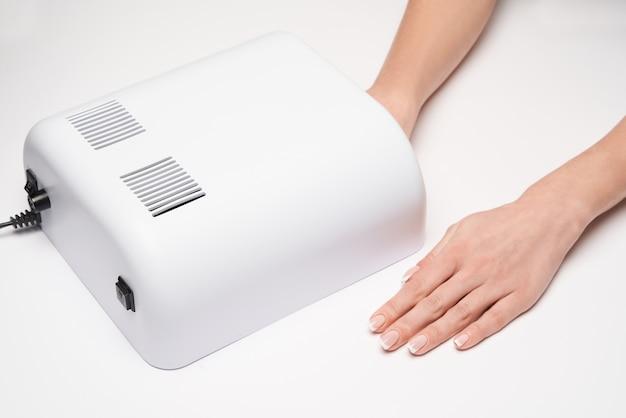 Hand mit uv-timer lampe lichter für nägel über lichtoberfläche