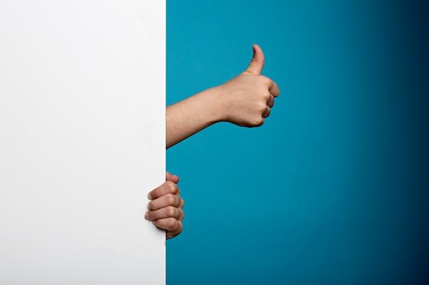 Hand mit weißem brett auf blauem backgorund