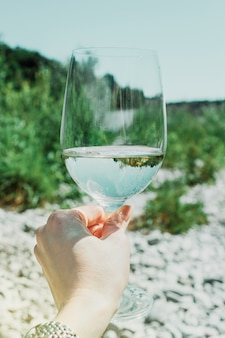 Hand mit weißweinglas auf dem grünen hintergrund der sommernatur