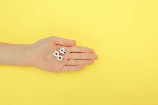 Hand mit würfeln auf gelbem grund.