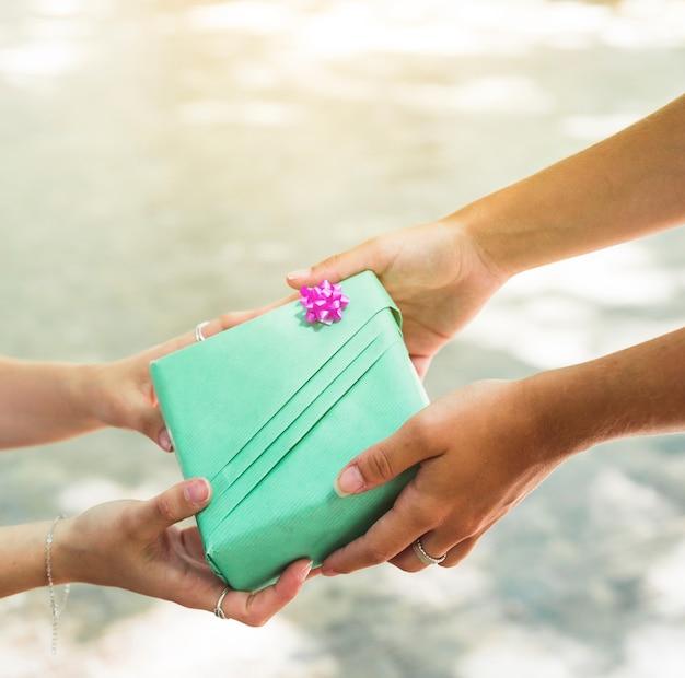 Hand mit zwei frauen, die grüne geschenkbox hält