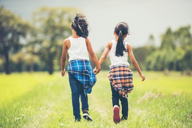Hand mit zwei kleinen mädchen, die zusammen hält, spaß im park habend