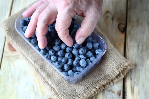 Hand nimmt blaubeeren vom tablett