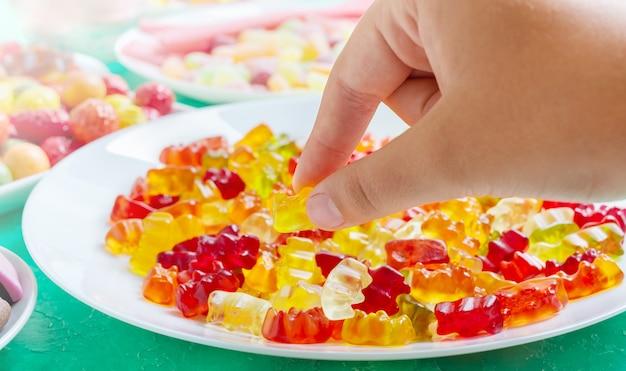 Hand nimmt bunte gummibärchen bonbons vom teller gelee-leckereien für kinder und erwachsene