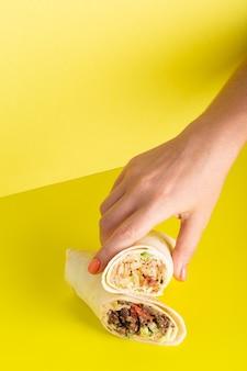 Hand nimmt dönerrollen-döner mit hühnchen und gemüse auf gelbem foto von hoher qualität