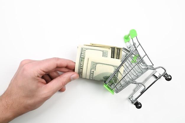 Hand nimmt dollar aus einem einkaufskorb. hochwertiges foto