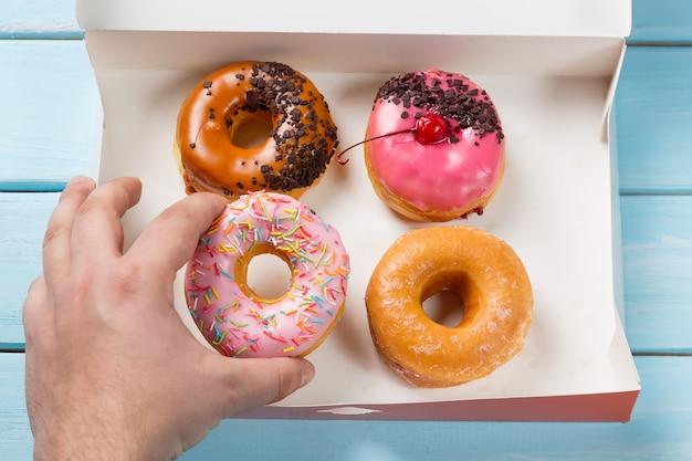 Hand nimmt donut aus der schachtel