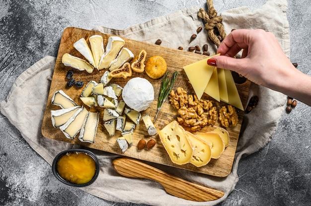Hand nimmt ein stück käse von einer käseplatte, die mit nüssen und feigen gedient wird. grauer hintergrund. ansicht von oben