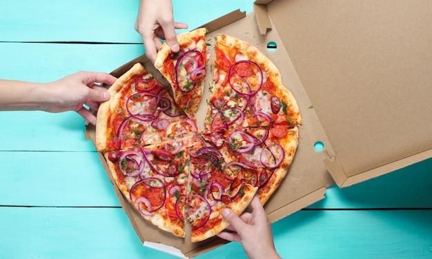 Hand nimmt ein stück pizza auf blauem tisch. firmenfreunde. freundlicher snack. draufsicht.