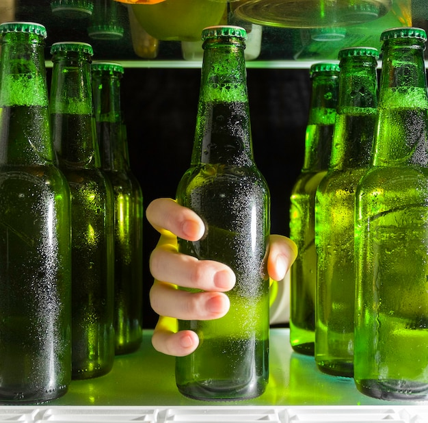 Hand nimmt eine flasche bier aus dem kühlschrank